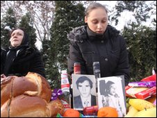 A Romanian woman kneels by photographs of a relative killed in 1989