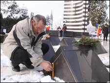 A man lights a candle at the heroes' cemetery in Timisoara