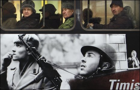 Romanians on a bus in Timisoara  covered with images of the 1989 revolution