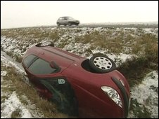 A car lies overturned in a ditch