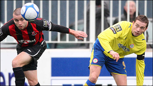 Crusaders captain Colin Coates in action against Chris Scannell of Cliftonville