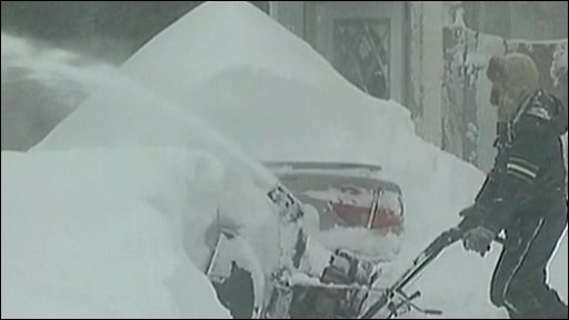 North Dakota resident clears snow from his house