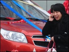 Woman passes a car for sale in Beijing, file image