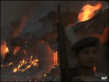 Soldier on guard near shops torched by rioters after bomb in Karachi on 28 December 2009