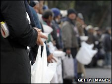 Homeless people queue for food