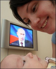 A mother tends her baby in St Petersburg as Prime Minister Vladimir Putin speaks on TV