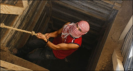 Gaza smuggler lowers himself into tunnel