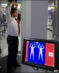 A man stands inside a body scanner as an image is displayed on a screen at Schiphol airport