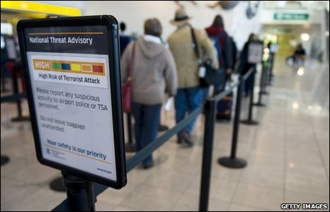 "Passengers pass by a sign stating the National Threat Advisory is at Level ""Orange,"" or high, outside a security screening area at Baltimore Washington International Airport December 29, 2009 in Baltimore, Maryland"