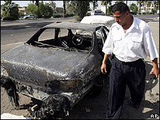 Iraqi security guard looks at car hit in the Nissor square shootings of September 2007