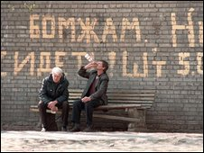 Russians drink vodka under sign saying 'Homeless, not allowed to sit here'
