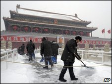Workers clear the snow outside Tiananmen Gate in Beijing