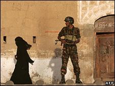 Woman walks past a soldier in Sanaa (file)