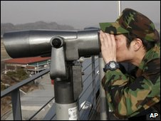 "South Korea""s army reserve soldier looks at the northern side through a pair of binoculars in Paj"