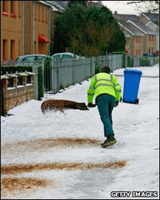 Worker spreading grit on a street in Glasgow on Monday 4 January