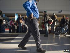 An airport security guard and passengers at Baltimore Washington International Airport