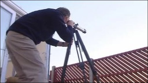 Brian Howells looking through a telescope
