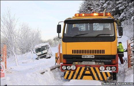 A snow plough attempts to dig out a refuse truck outside Llandegla Forest