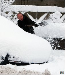 A man clears snow from his car in St Boswells, the Scottish Borders