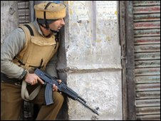 An Indian policeman takes cover during firing in Srinagar on January 6, 2010.