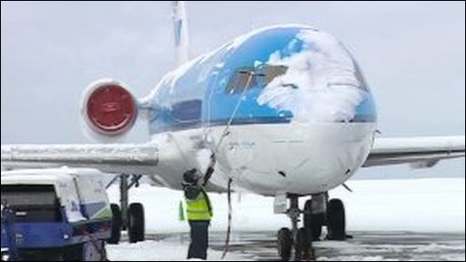 Man clearing snow of plane
