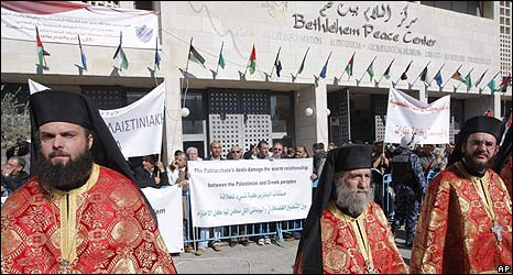 Orthodox priests attend festivities in Bethlehem in front of protest banners (06.01.10)