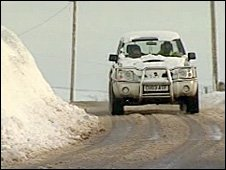 A 4x4 vehicle on a slush-covered rural road