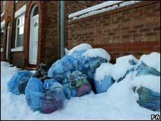 Snow-covered bin bags in Greater Manchester