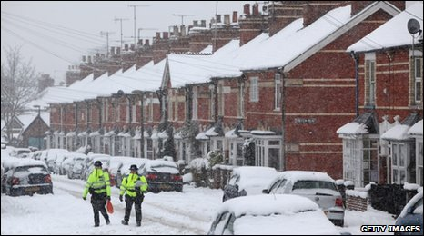 Police Community Support Officers walk through snow to check whether any elderly residents need help in Henley, Oxfordshire