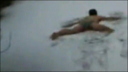 A young man in his underwear making a snow angel