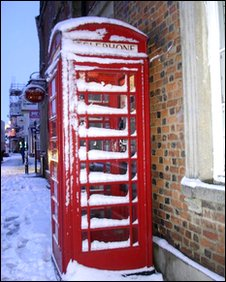 Red phone box covered in snow.