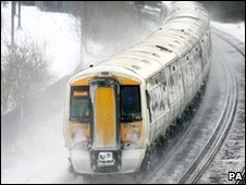 A train travels through the snow in Ashford in Kent