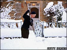 Man clearing snow off his path in the UK