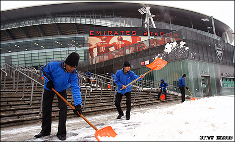 Staff try to move snow from outside the Emirates Stadium on Wednesday
