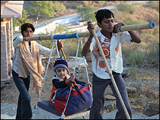 Jain boys carry a small child up the hill