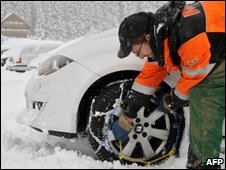 A man fitting snow chains in Germany