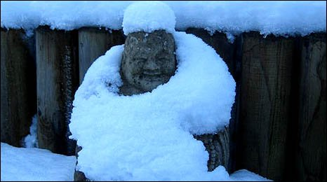 image shows a garden statue of Buddha coated in snow - image by Anne Beyer
