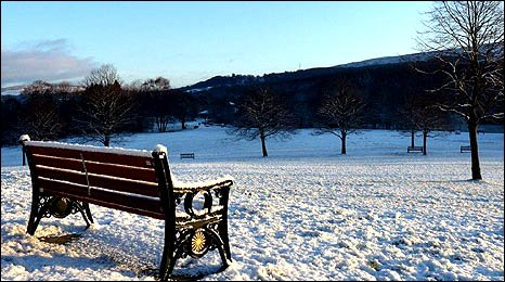 Image of a snow-covered bench and landscape at the Gnoll Country Park in Neath - by Mike Davies.