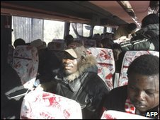 Immigrant workers board a bus to be evacuated from Rosarno