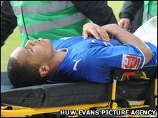 Cardiff City striker Josh Magennis is stretchered off in the first half