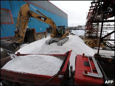 A digger pours salt into a waiting truck