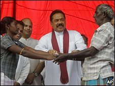 Sri Lankan President Mahinda Rajapakse, centre, hands over a Tamil former child combatant to her father, 9 January 2010