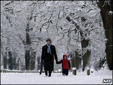 A man walks with his daughter after discovering her primary school is closed in Hartley Wintney, in Hampshire, on 6 January 2010