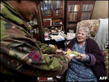 A member of the British Army 36 Royal Engineer Gurkha regiment hands a meal to an elderly woman in Chatham, Kent