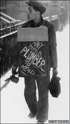 December 1938: A plumber advertising his services as he walks a snowy street.