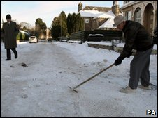 A man scrapes snow and ice from a road