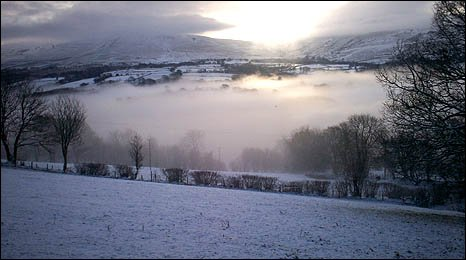 Image taken from Gwynfe by June Madeira-Cole of the mist over the Black Mountains and snow-covered fields