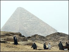Egyptian archaeology workers dig tombs in front of the Great  Pyramid in Giza, Egypt