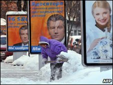 A woman cleans snow away from pre-election posters in Kiev