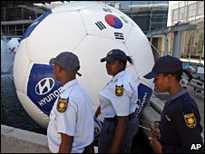 South African police officers walk past giant football (file photo)